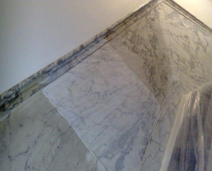 Gedeeltelijk gereinigde Bianco Carrara lambrisering van een monumentale trap.