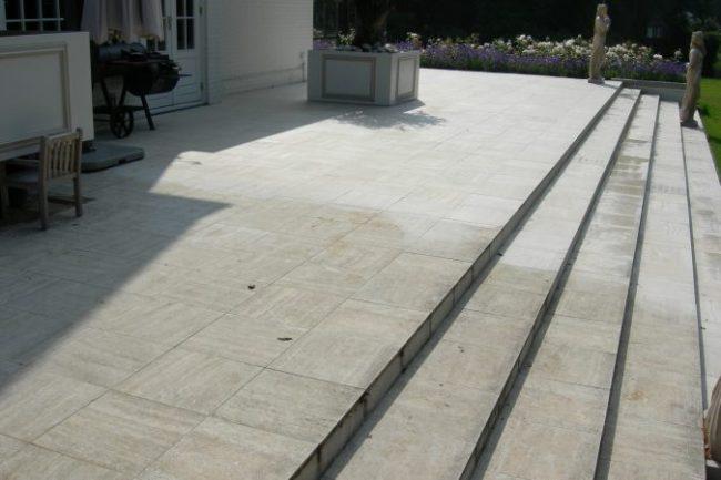 Deels gereinigd natuursteen buitenterras. Voorzijde is voor de behandeling, aan de achterzijde kunt u zien hoe schoon het wordt.