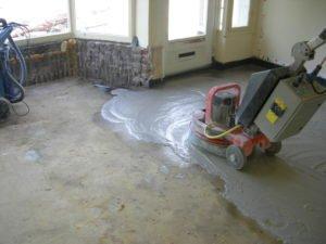 Onder de lijmlaag ligt een prachtige granito vloer. De lijmlaag wordt hier weg geschuurd.