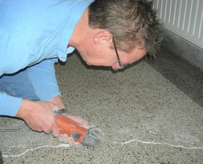 De scheur in de granito vloer wordt eerst schoongemaakt om deze goed te repareren