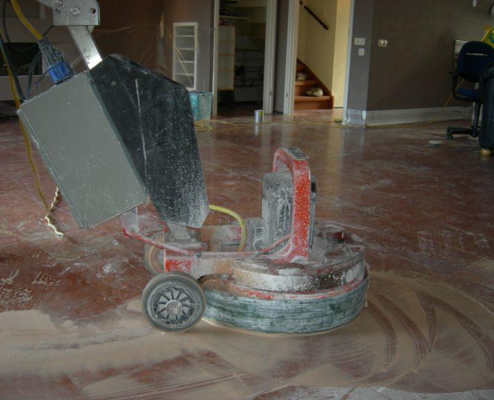 De vloer wordt geschuurd met water en diamant schuurschijven onder de machine