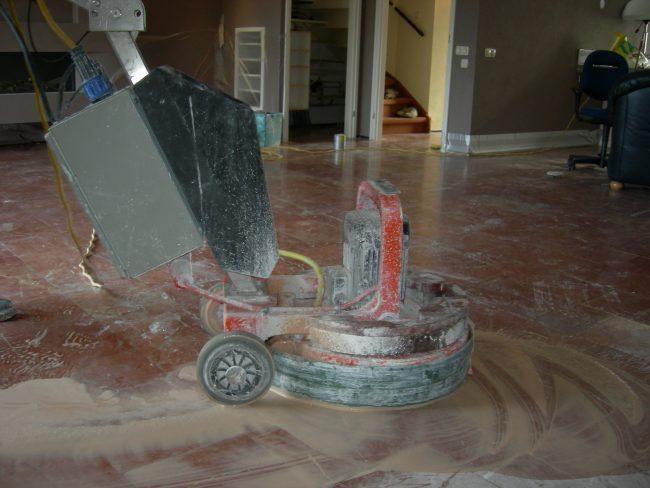 De vloer wordt geschuurd met diamant schuurschijven onder de machine en water.